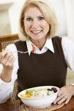 Ältere Frau, die das Abendessen, lächelnd an der Kamera isst Lizenzfreies Stockfoto