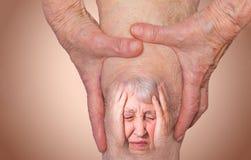 Ältere Frau, die das Knie mit den Schmerz hält stockfoto