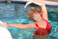 Ältere Frau, die in das Pool ausdehnt Stockfoto