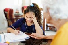 Ältere Frau, die dem kleinen Mädchen tut Schulhausarbeit hilft Stockfoto