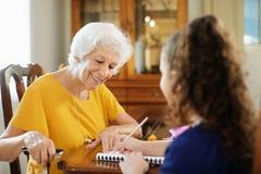 Ältere Frau, die dem kleinen Mädchen tut Schulhausarbeit hilft Lizenzfreie Stockfotografie
