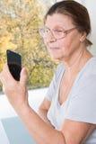 Ältere Frau, die den Schirm des Handys und des Lächelns betrachtet Stockfotografie
