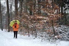 Ältere Frau, die in den Schnee geht stockfotografie