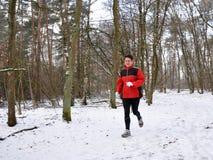 Ältere Frau, die in den Schnee läuft stockbild