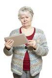 Ältere Frau, die den Tablettencomputer schaut verwirrt verwendet Stockbilder