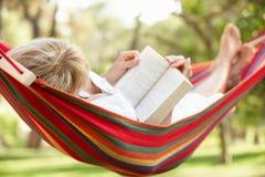 Ältere Frau, die in der Hängematte mit Buch sich entspannt Stockbild