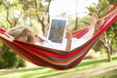 Ältere Frau, die in der Hängematte mit E-Buch sich entspannt Lizenzfreie Stockfotos
