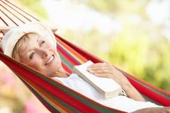 Ältere Frau, die in der Hängematte sich entspannt lizenzfreie stockfotos