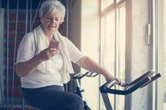 Ältere Frau, die in der Turnhalle ausarbeitet stockfotografie