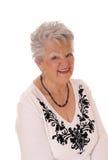 Ältere Frau, die die Kamera, lächelnd untersucht Stockbild
