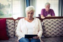 Ältere Frau, die digitale Tablette verwendet Stockbilder
