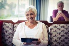 Ältere Frau, die digitale Tablette verwendet Stockfotos