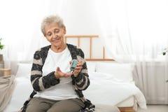 Ältere Frau, die digitales glucometer verwendet Diabetes-Steuerung lizenzfreies stockfoto