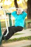 Ältere Frau, die draußen Übungen tut Stockbild