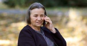 Ältere Frau, die draußen auf Smartphone spricht stock video