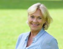 Ältere Frau, die draußen lächelt Lizenzfreies Stockfoto