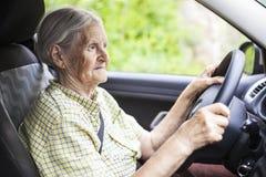 Ältere Frau, die ein Auto antreibt stockbilder