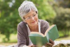 Ältere Frau, die ein Buch am Park liest Stockfoto