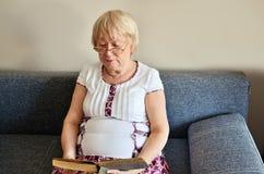 Ältere Frau, die ein Buch sitzt auf der Couch horizontal liest Lizenzfreies Stockfoto