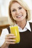 Ältere Frau, die ein Glas Orangensaft trinkt Stockbilder
