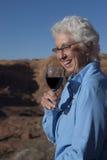 Ältere Frau, die ein Glas Wein genießt Lizenzfreie Stockfotografie