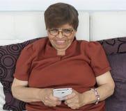 Ältere Frau, die ein on-line spielt stockfotos