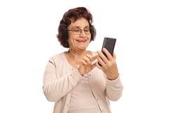 Ältere Frau, die ein Telefon und ein Lächeln verwendet Stockfoto