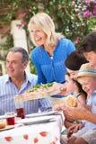 Ältere Frau, die eine Familien-Mahlzeit dient Stockfotografie