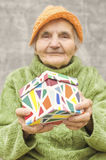 Ältere Frau, die eine Geschenkbox hält Lizenzfreie Stockfotos