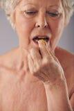 Ältere Frau, die eine Pille einnimmt Stockbild