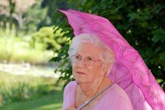 Ältere Frau, die in einem Garten stillsteht Lizenzfreie Stockfotos