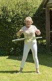 Ältere Frau, die in einem Garten trainiert lizenzfreie stockfotografie
