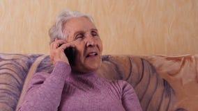 Ältere Frau, die an einem Handy beim Sitzen auf einer Couch spricht Er steht durch Handy, Smartphone in Verbindung stock video