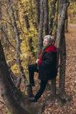 Ältere Frau, die in einem Herbstpark aufwirft Stockbilder
