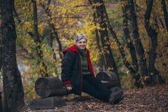 Ältere Frau, die in einem Herbstpark aufwirft Stockbild