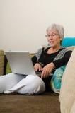 Ältere Frau, die an einem Laptop arbeitet lizenzfreie stockfotos