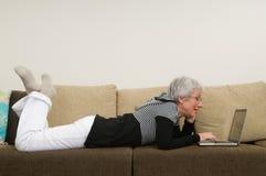 Ältere Frau, die an einem Laptop arbeitet lizenzfreie stockbilder