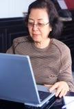 Ältere Frau, die an einem Laptop arbeitet Stockfotografie