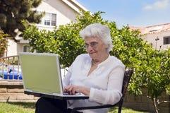 Ältere Frau, die einen Laptop verwendet stockbild