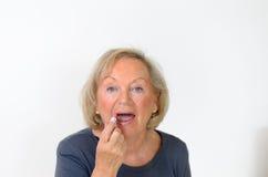 Ältere Frau, die einen natürlichen Schatten des Lippenstifts anwendet Lizenzfreies Stockfoto