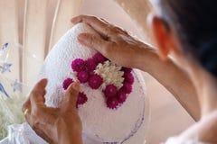 Ältere Frau, die einen Sockel Folwers-Behälter für ein Innenereignis in Handarbeit macht stockfoto