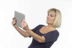 Ältere Frau, die einen Tablettencomputer verwendet lizenzfreies stockbild
