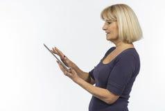 Ältere Frau, die einen Tablettencomputer verwendet stockfotos