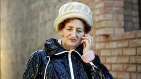 Ältere Frau, die einen Telefonanruf mit ihrem Handy im Freien macht stock video footage