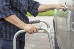 Ältere Frau, die einen Wanderer am Parkplatz verwendet Stockbild