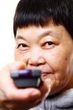 Ältere Frau, die entfernte Station von Fernsehapparat verwendet Lizenzfreie Stockfotos