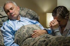 Ältere Frau, die für ihren kranken Ehemann betet Lizenzfreie Stockfotografie