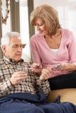 Ältere Frau, die für kranken Ehemann sich interessiert Stockfotografie