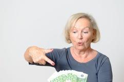 Ältere Frau, die Fan von Euros mit den Daumen oben hält Stockfoto