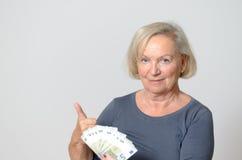 Ältere Frau, die Fan von Euros mit den Daumen oben hält Stockfotografie